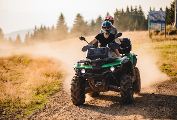 Two people ride on an ATV through a dusty field.