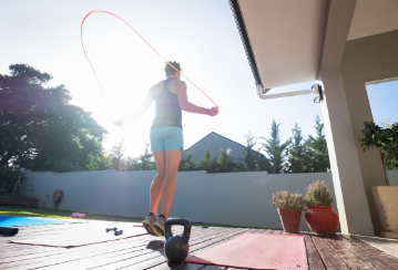 A person jumps rope outside on their deck during a sunny day.