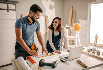 Couple stands in front of a work bench with blueprints on it, smiling and excited to get to work. Construction materials are all around them.