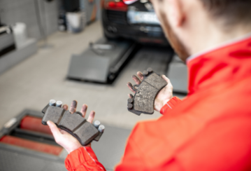 A mechanic holds a new brake pad in one hand and a worn one in the other while standing in a mechanic shop.