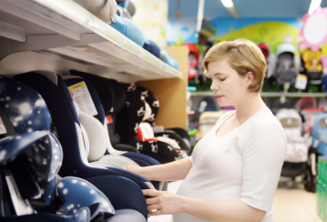 A woman looks at car seats in the isle of a store.