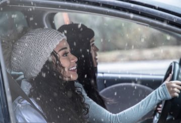 Two smiling ladies sitting in a car driving through light snow.